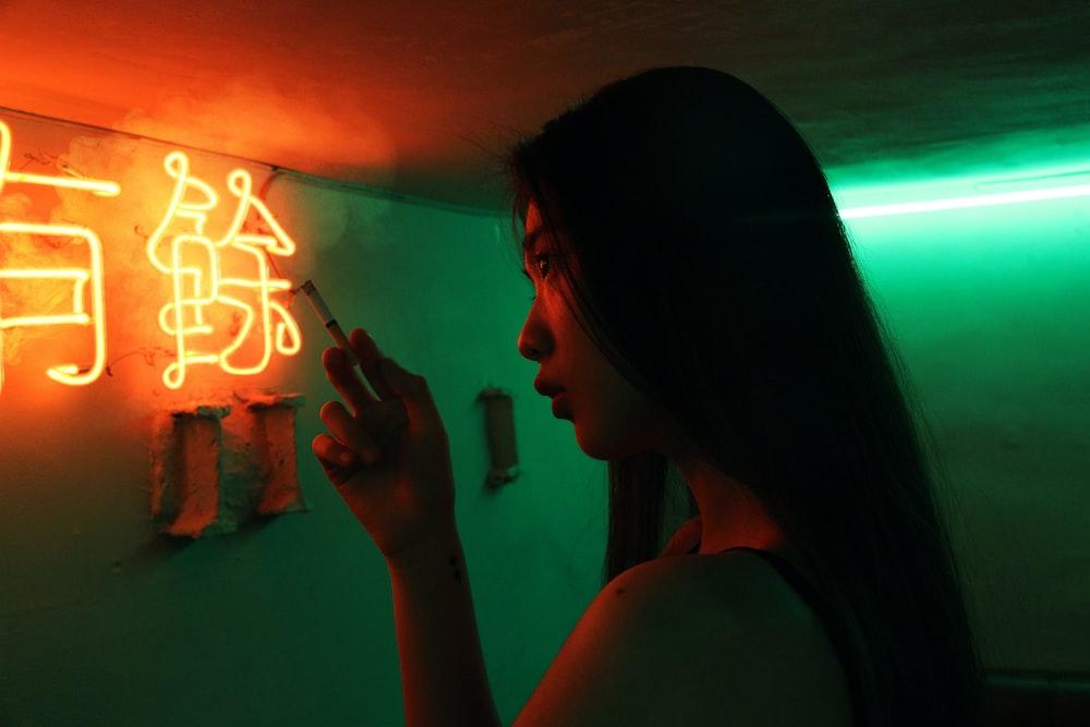 woman holding single cigarette inside room