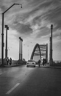 grayscale photography of bridge with vehicle and people walking