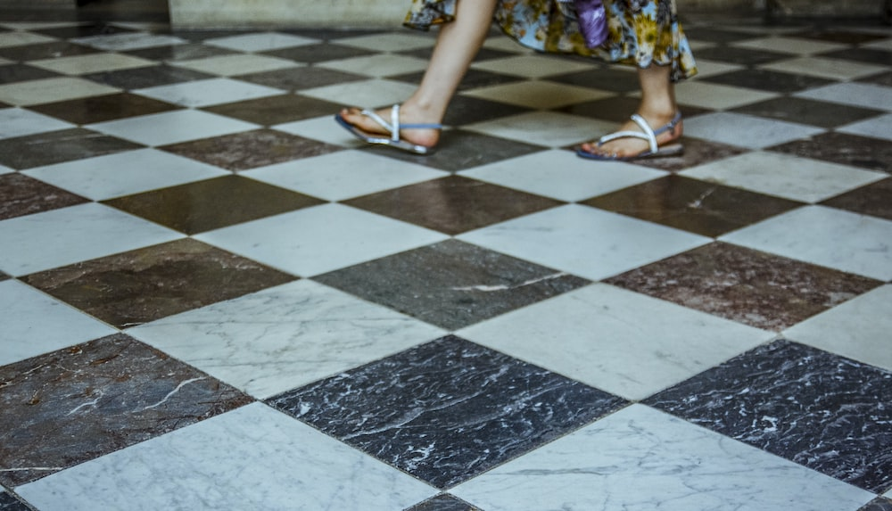 Person Walking On Checked Tiles Photo