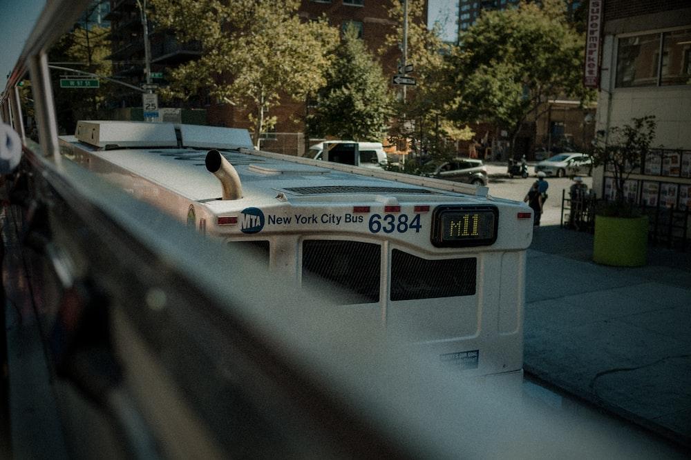 white New York City bus on road during daytime
