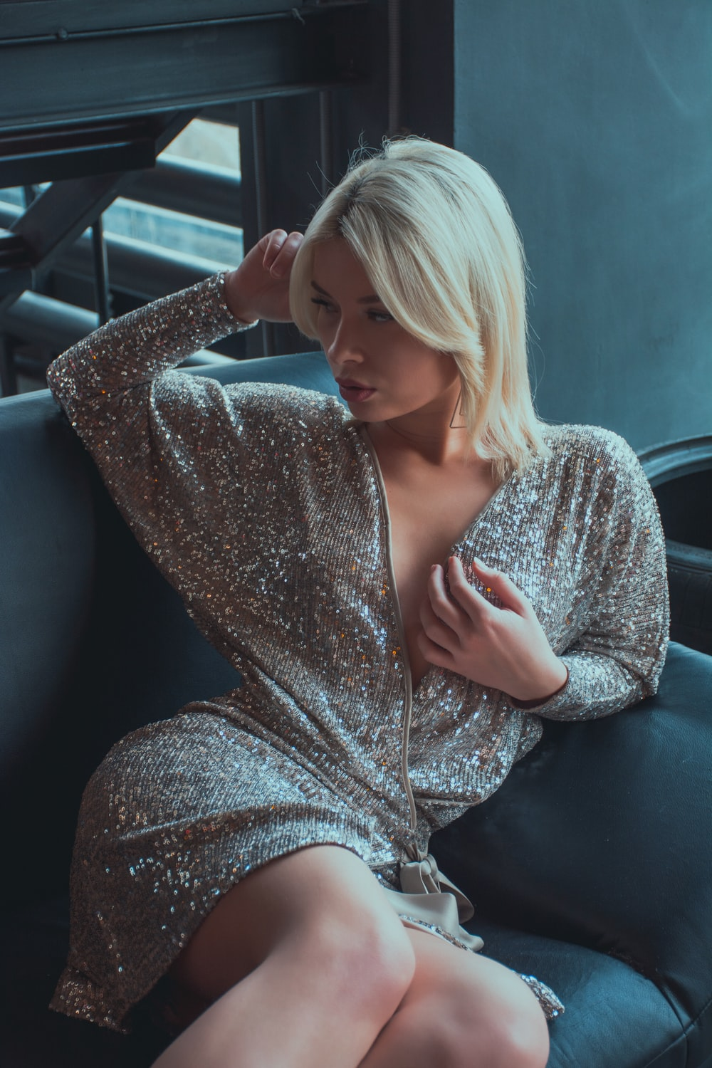 woman sitting on sofa wearing sequined long-sleeved mini dress
