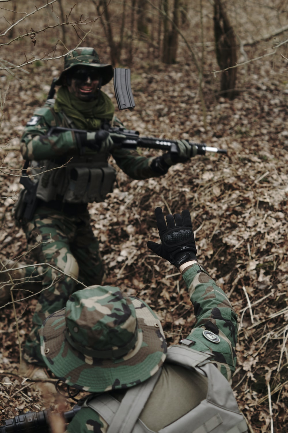 man holding assault rifle in the middle of forest