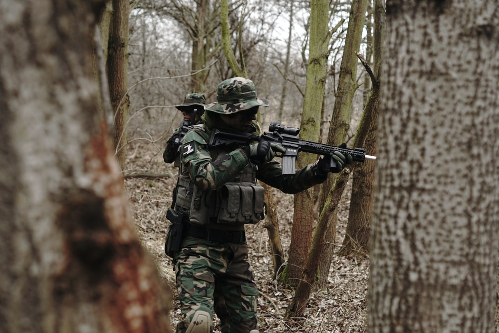 soldier holding assault rifle in forest