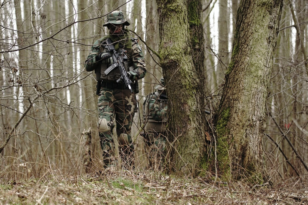 man holding rifle near the tre