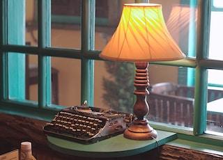 gray typewriter beside table lamp near window