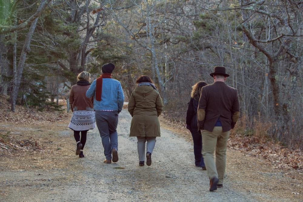 five people walking between trees