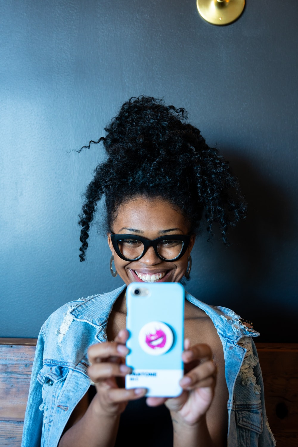 smiling woman while holding smartphone
