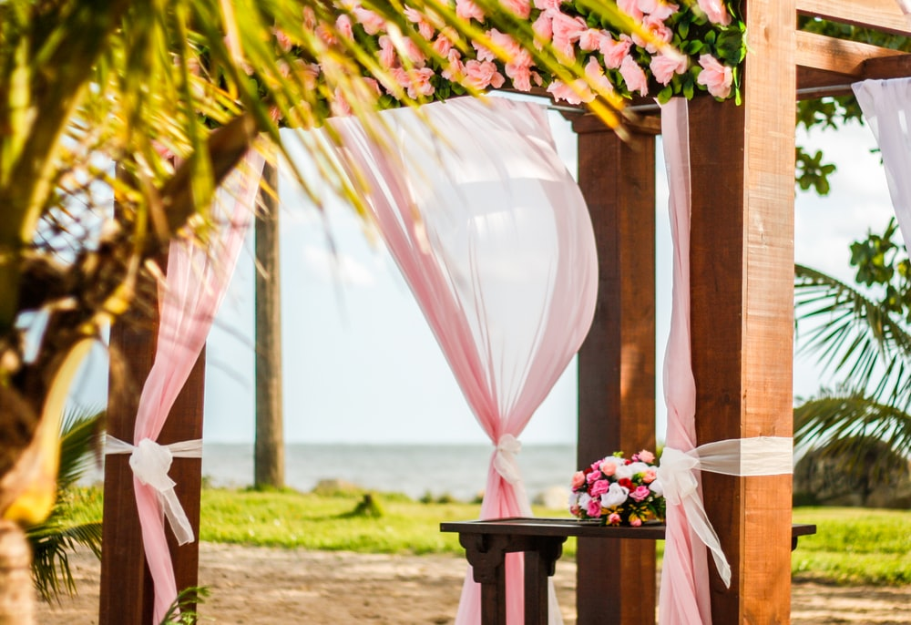 brown wooden gazebo with pink curtain