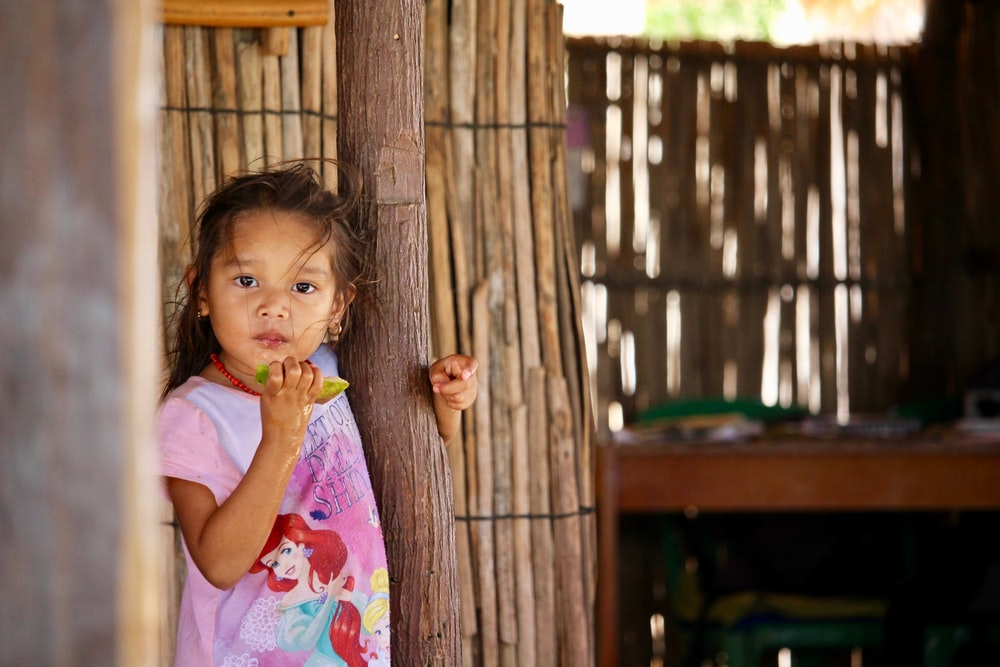 shallow focus photo of girl leaning on wooden post
