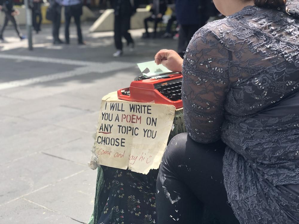 person suing red typewriter