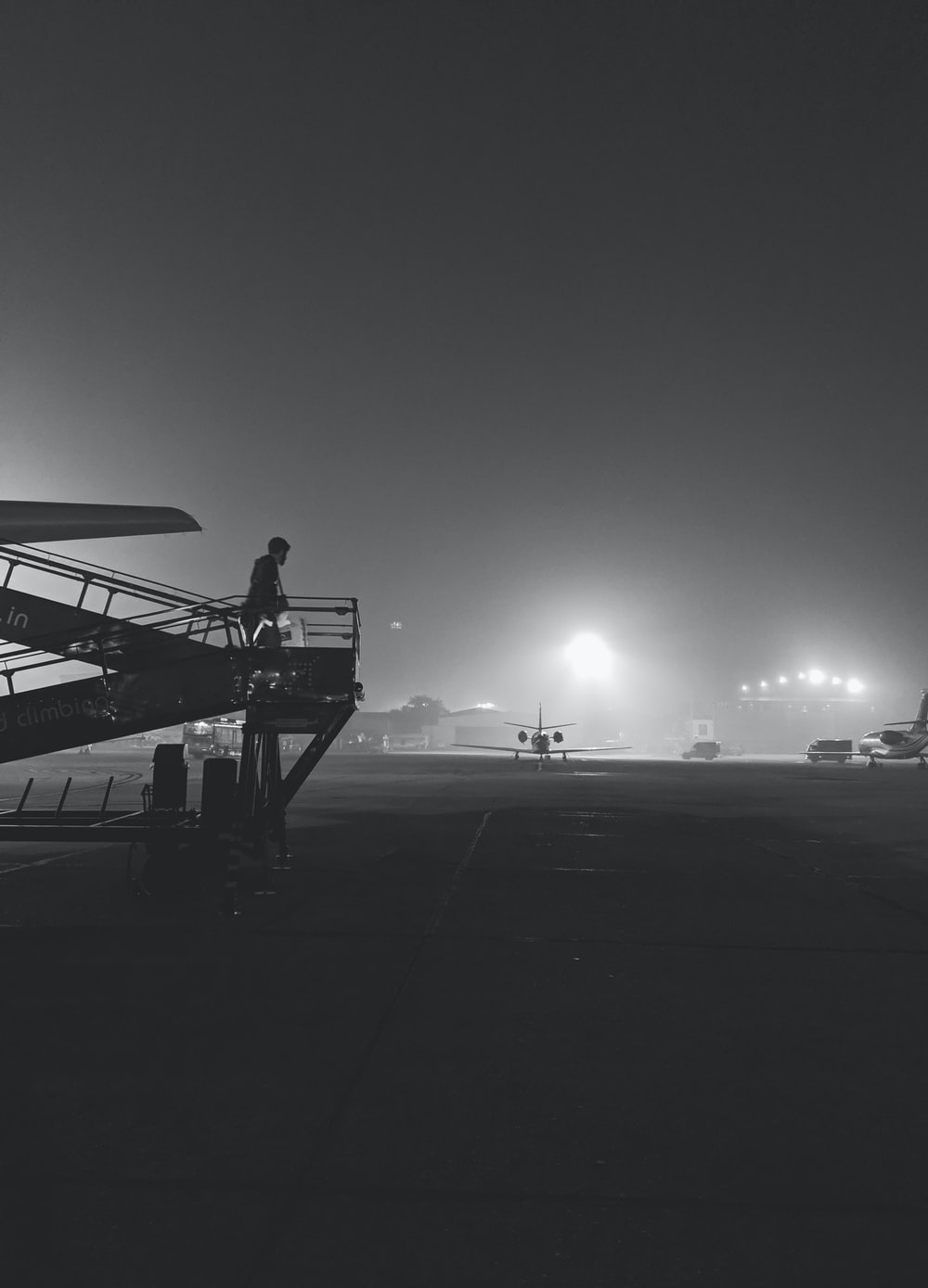 grayscale photography of person walking on airliner stairs
