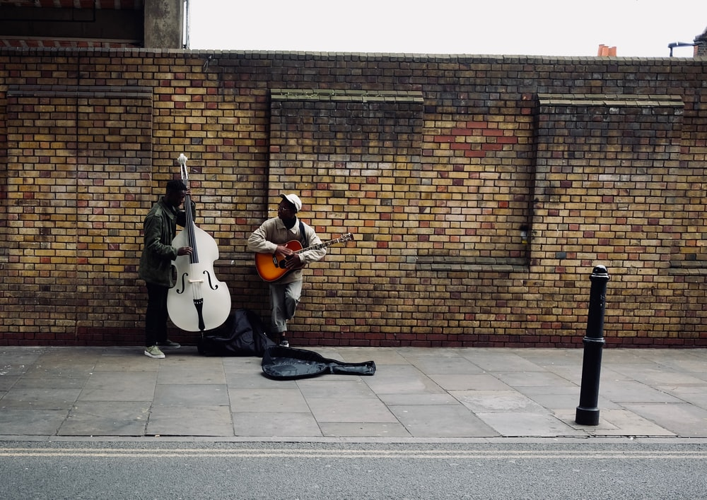 two men playing string instruments beside road