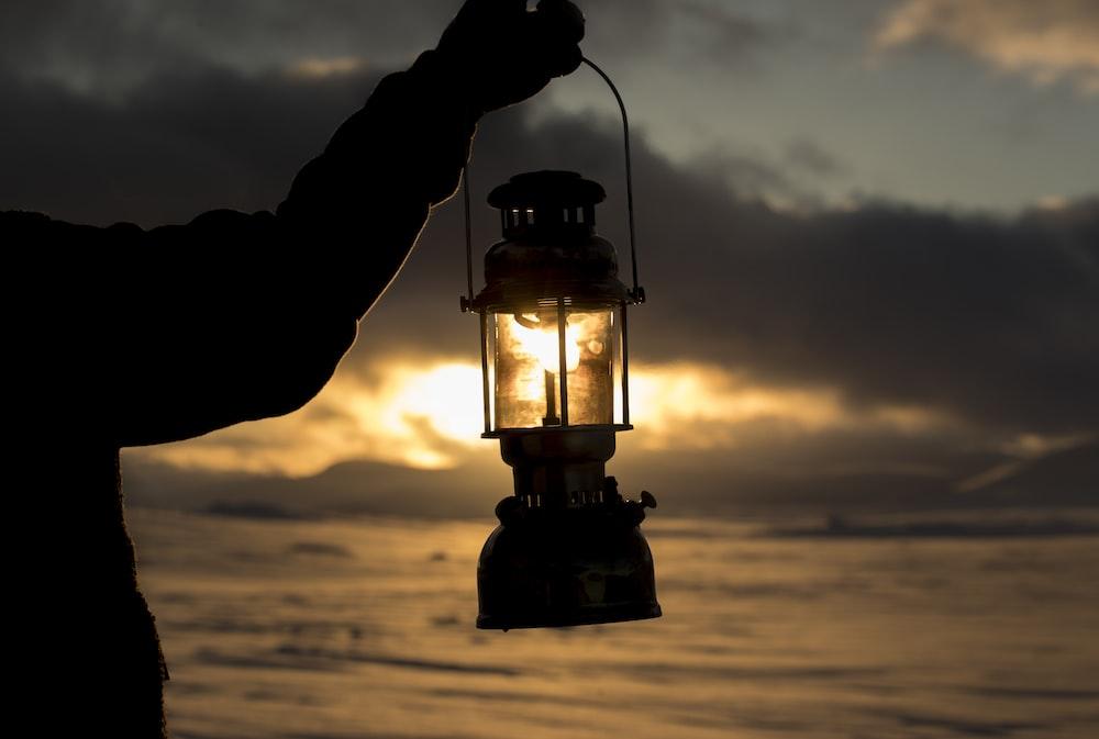 person standing on seashore and holding kerosene lantern lamp during sunset
