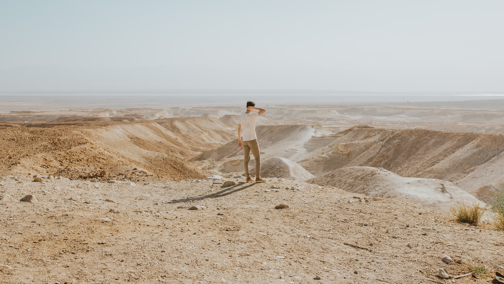 man standing at the desert during day