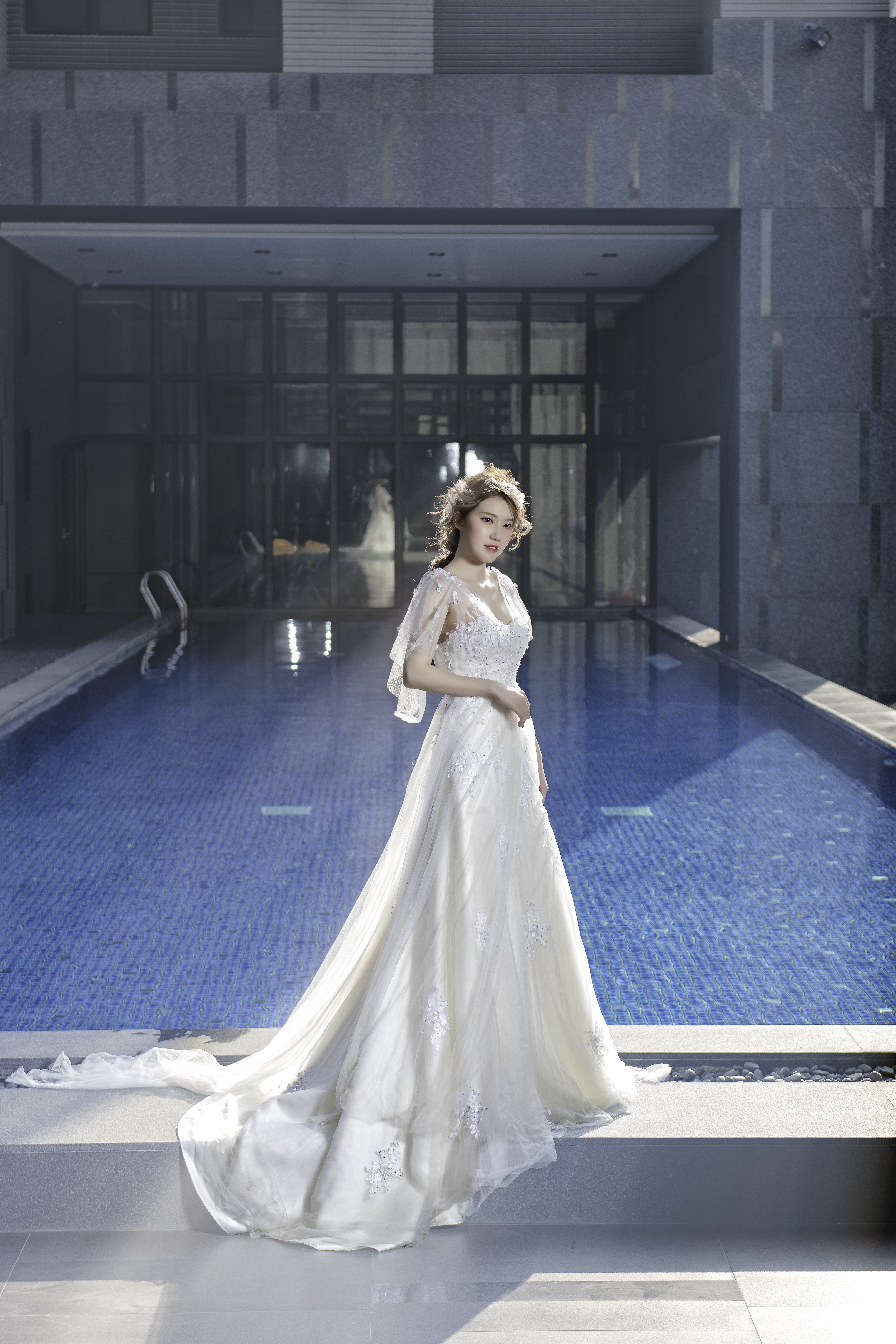 woman in white dress standing near swimming pool during daytime