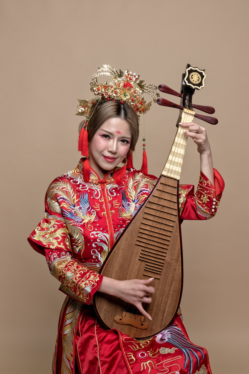 woman holding string instrument while smiling