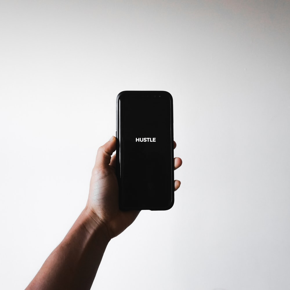 person holding phone with hustle text