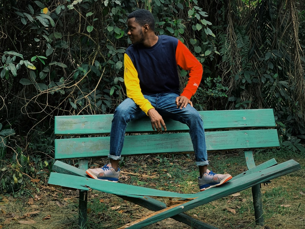 man in yellow, red, and black long-sleeved shirt and blue jeans sitting on wrecked bench backrest