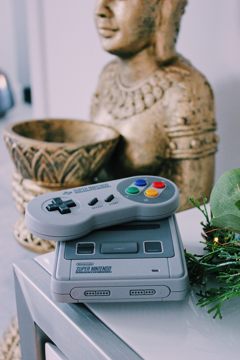 gray Super Nintendo game console with controller on table