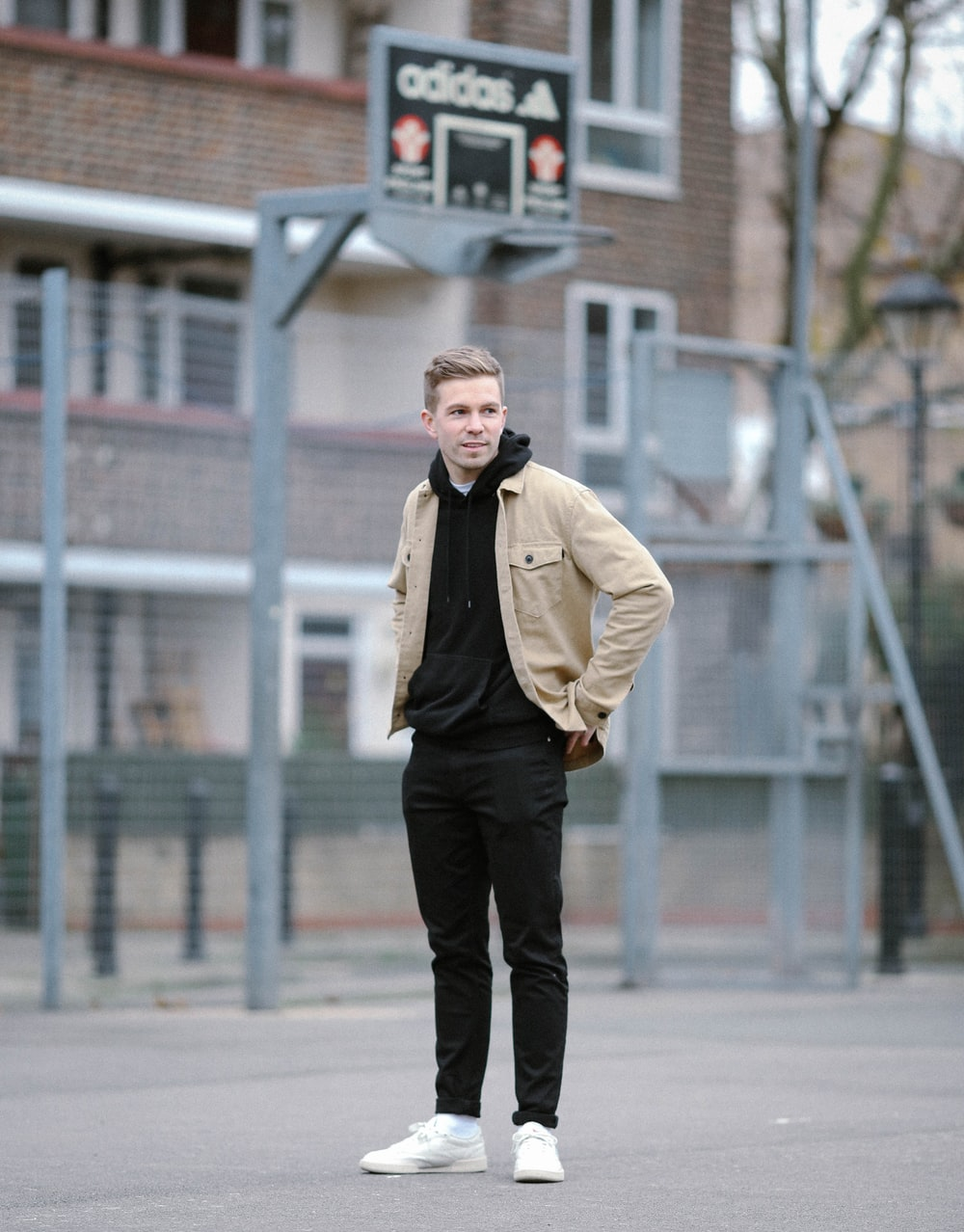 man wearing brown jacket and black pants standing near basketball ring