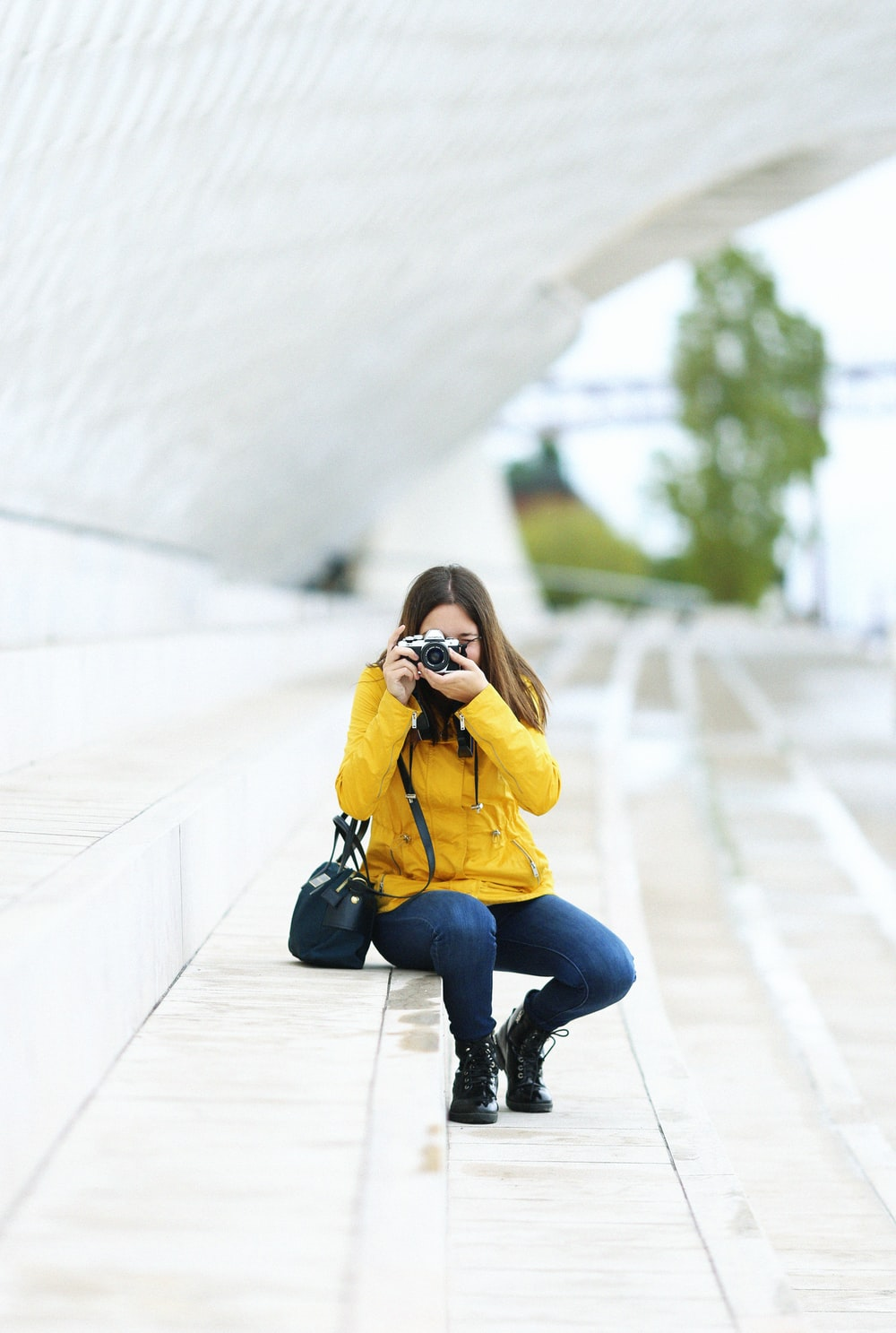 woman sitting on stair and capturing photo