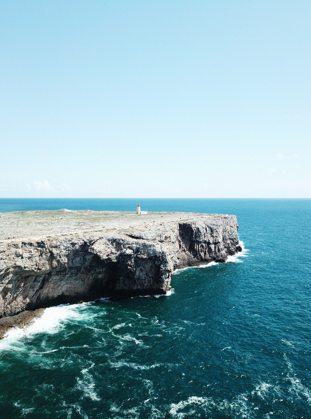 person standing on rock formation cliff beside sea