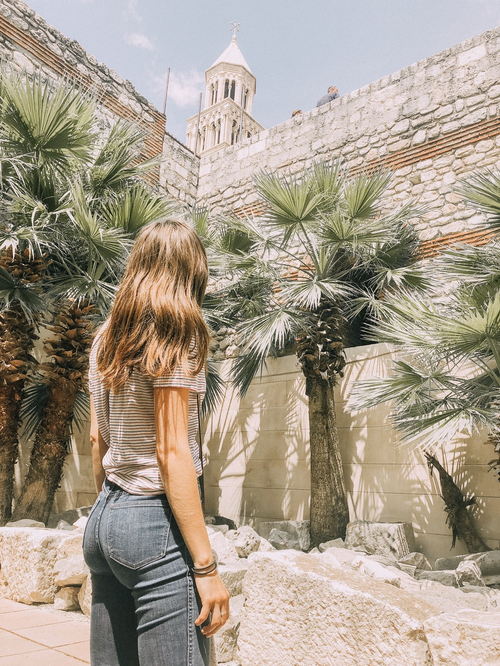 woman standing near palm trees and concrete wall during daytime