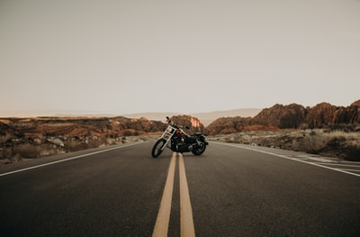 black cruiser motorcycle at the middle of the road