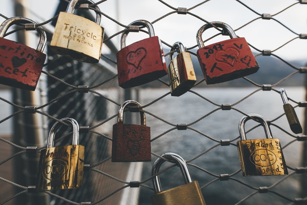 assorted-color padlocks on fence during daytime