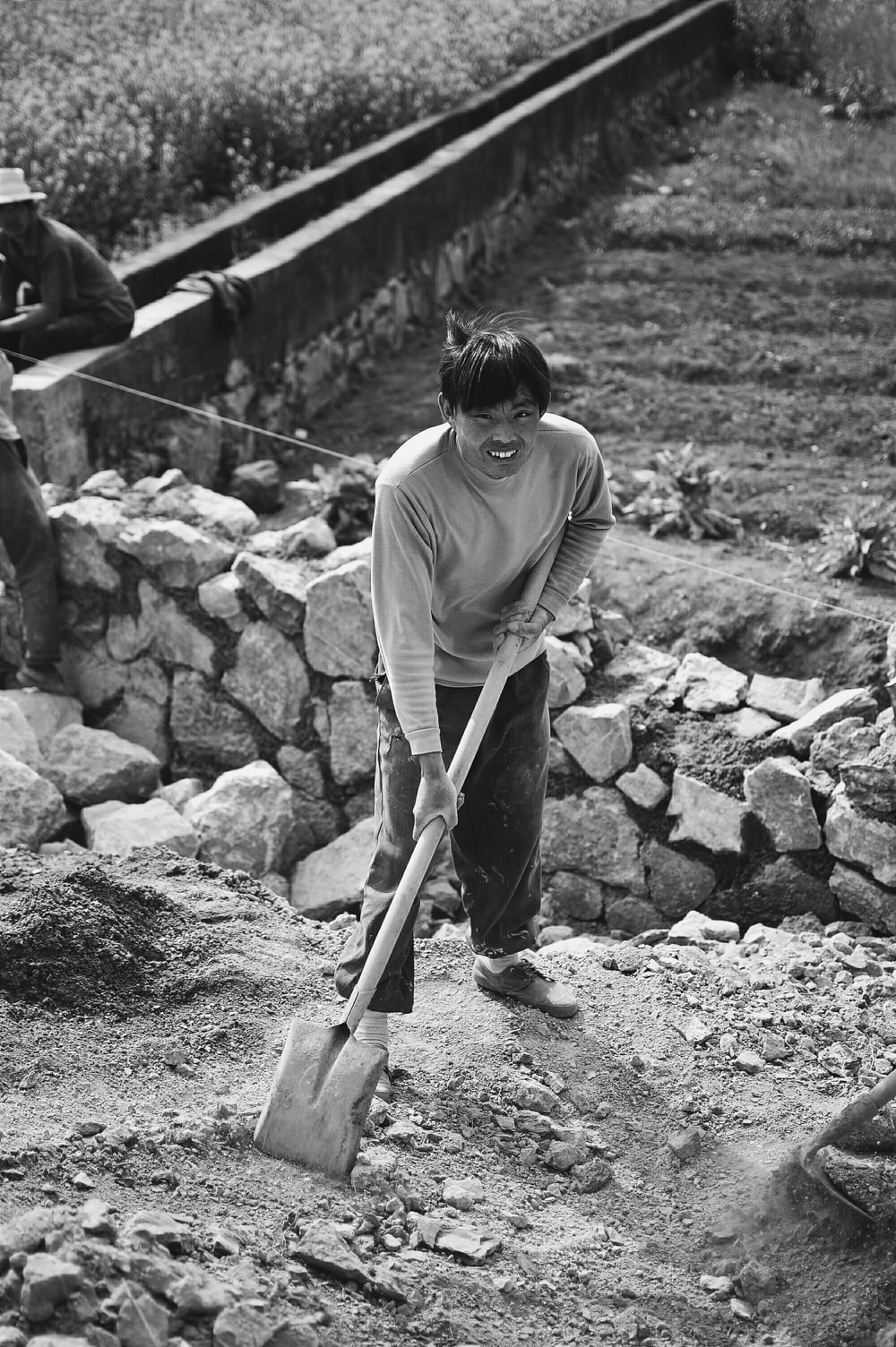 grayscale photo of man holding shovel