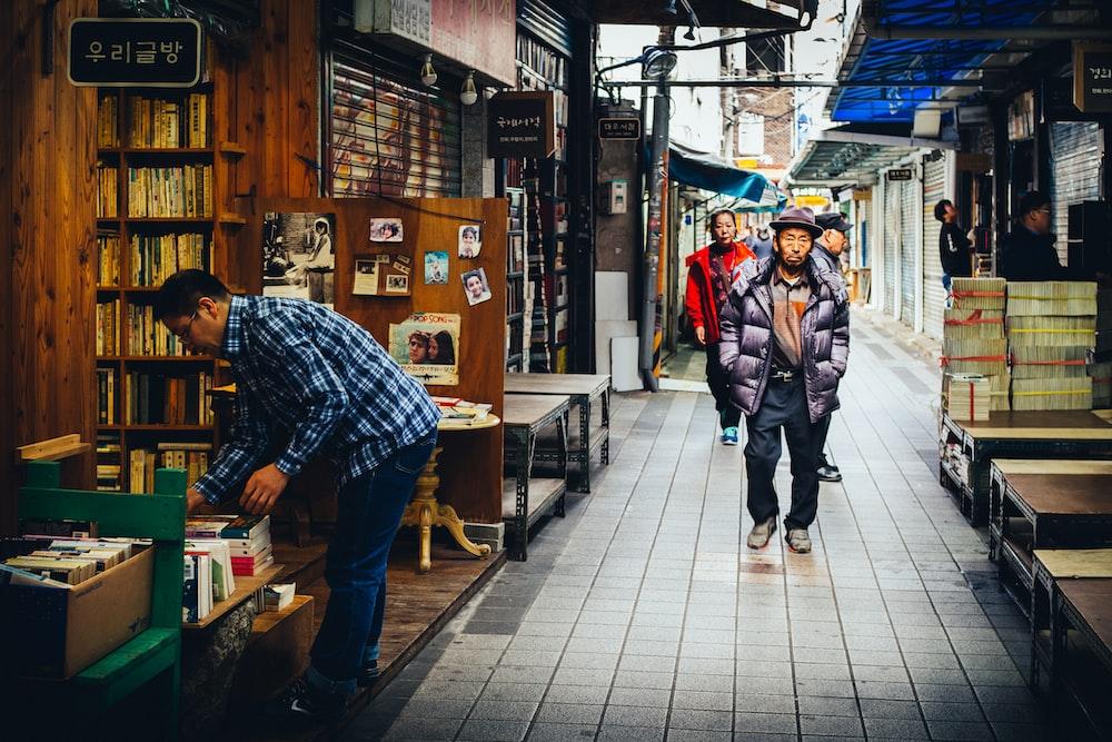 men walking along narrow pathway in market
