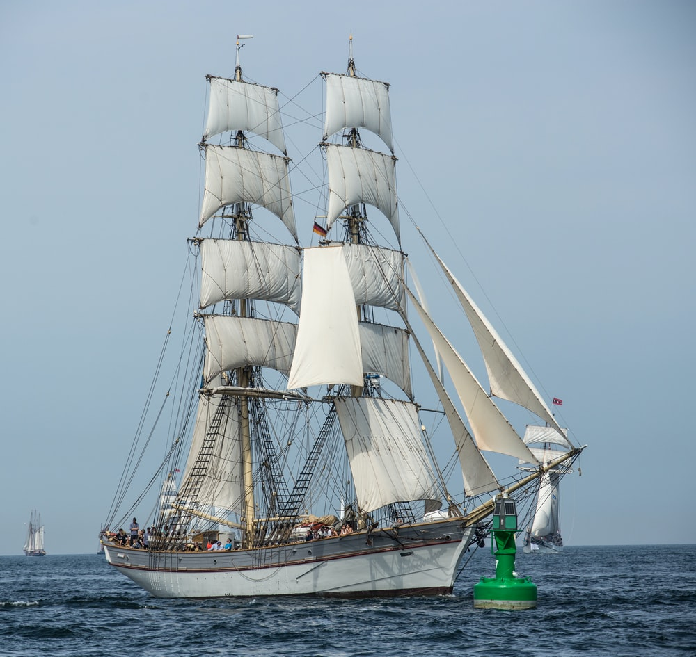 white clipper ship on body of water during daytime