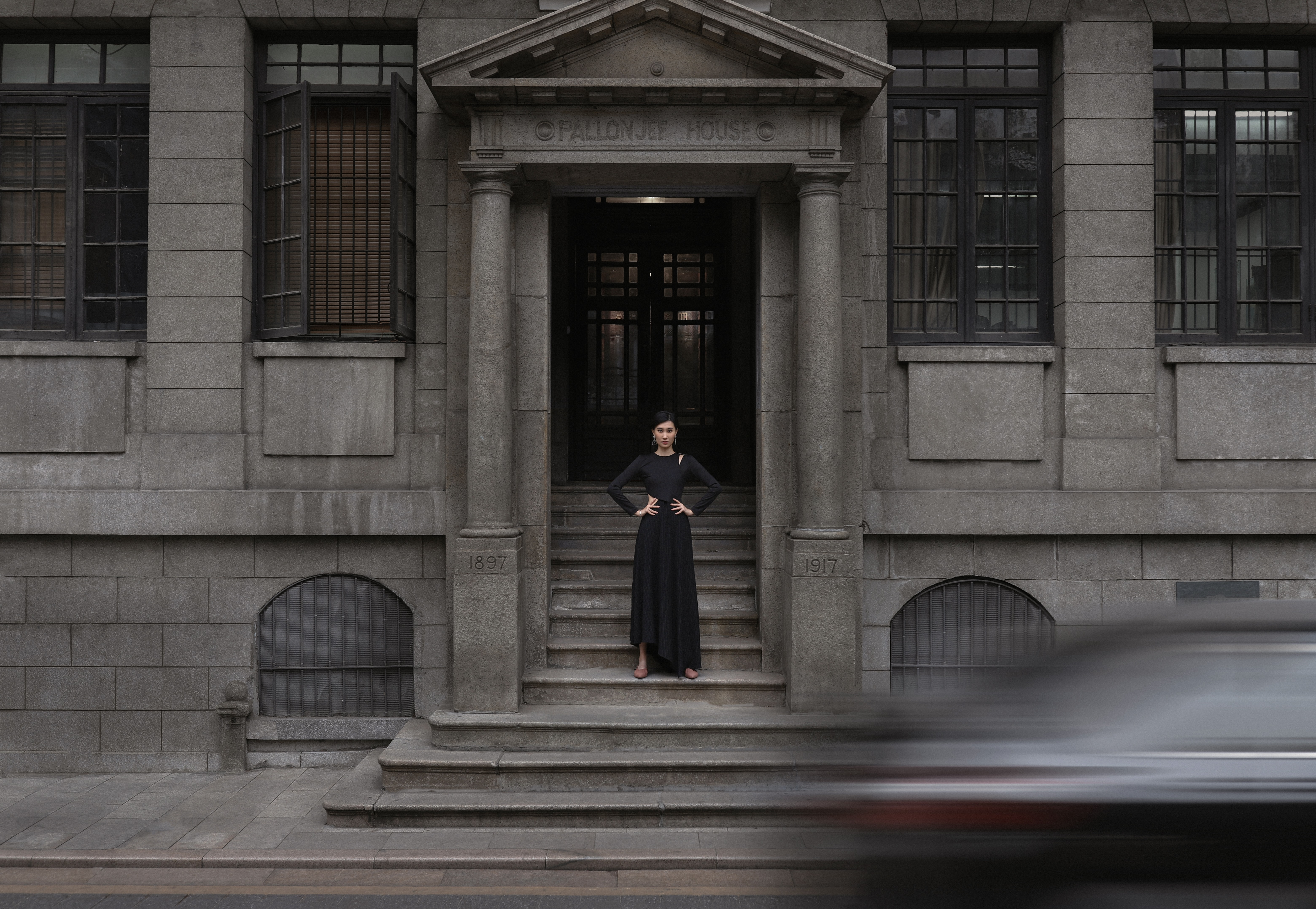 woman standing in front of gray concrete building
