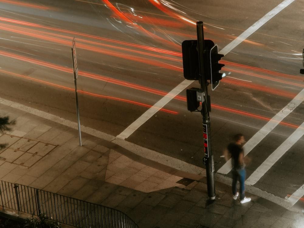 man standing beside black traffic light