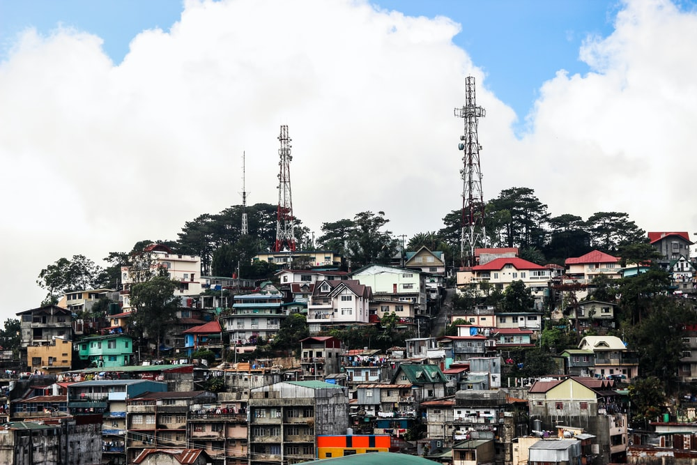 houses near satellite tower during daytime