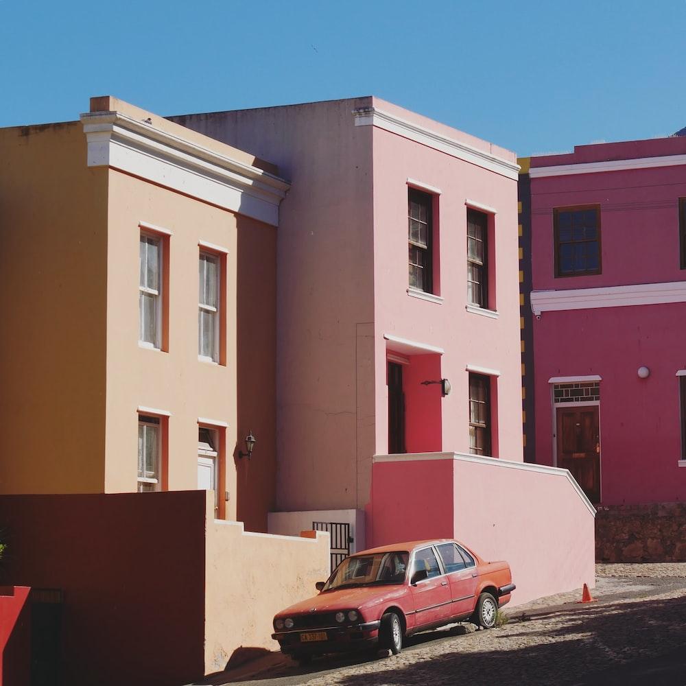 pink sedan parked on road