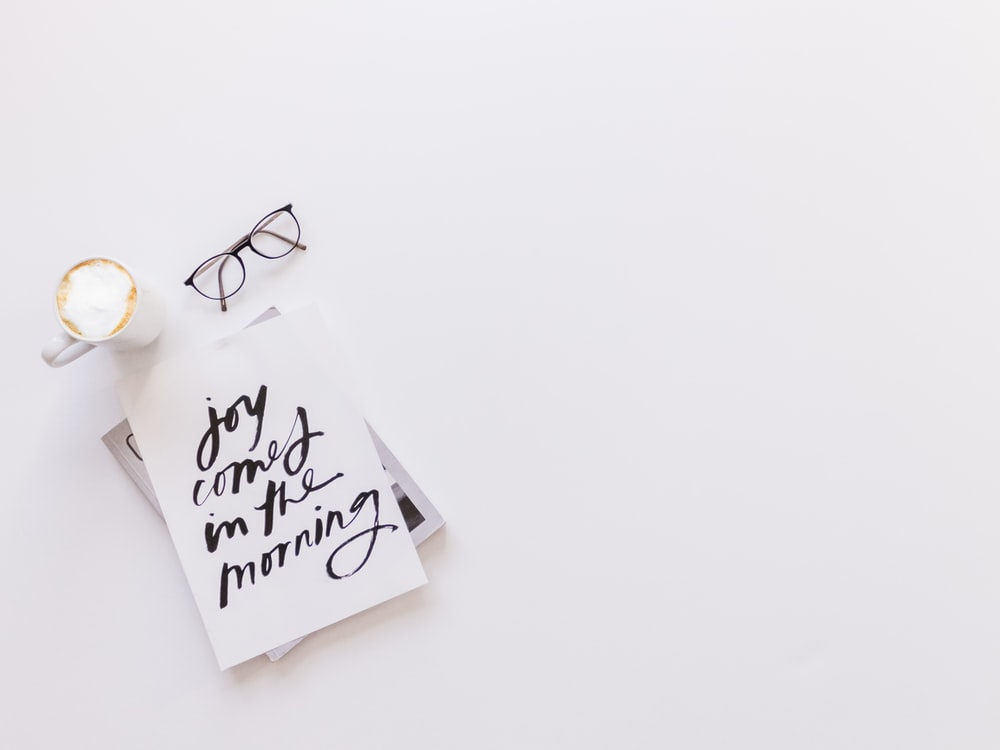 joy comes in the morning card beside coffee and eyeglasses