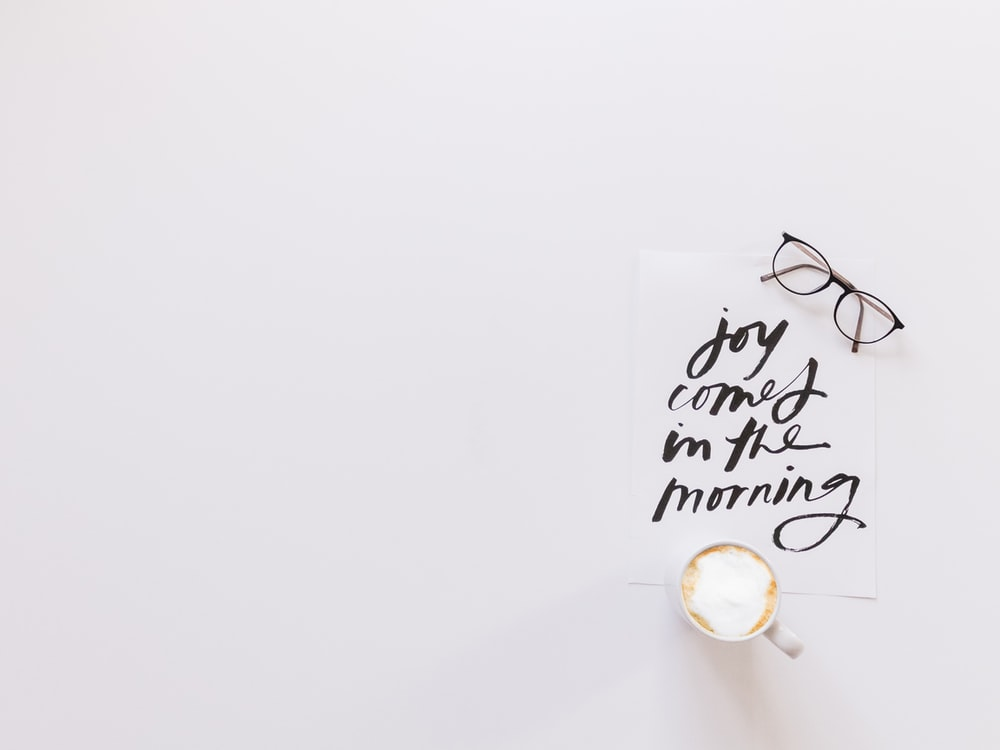 brown eyeglasses and latte on top of joy comes in the morning note