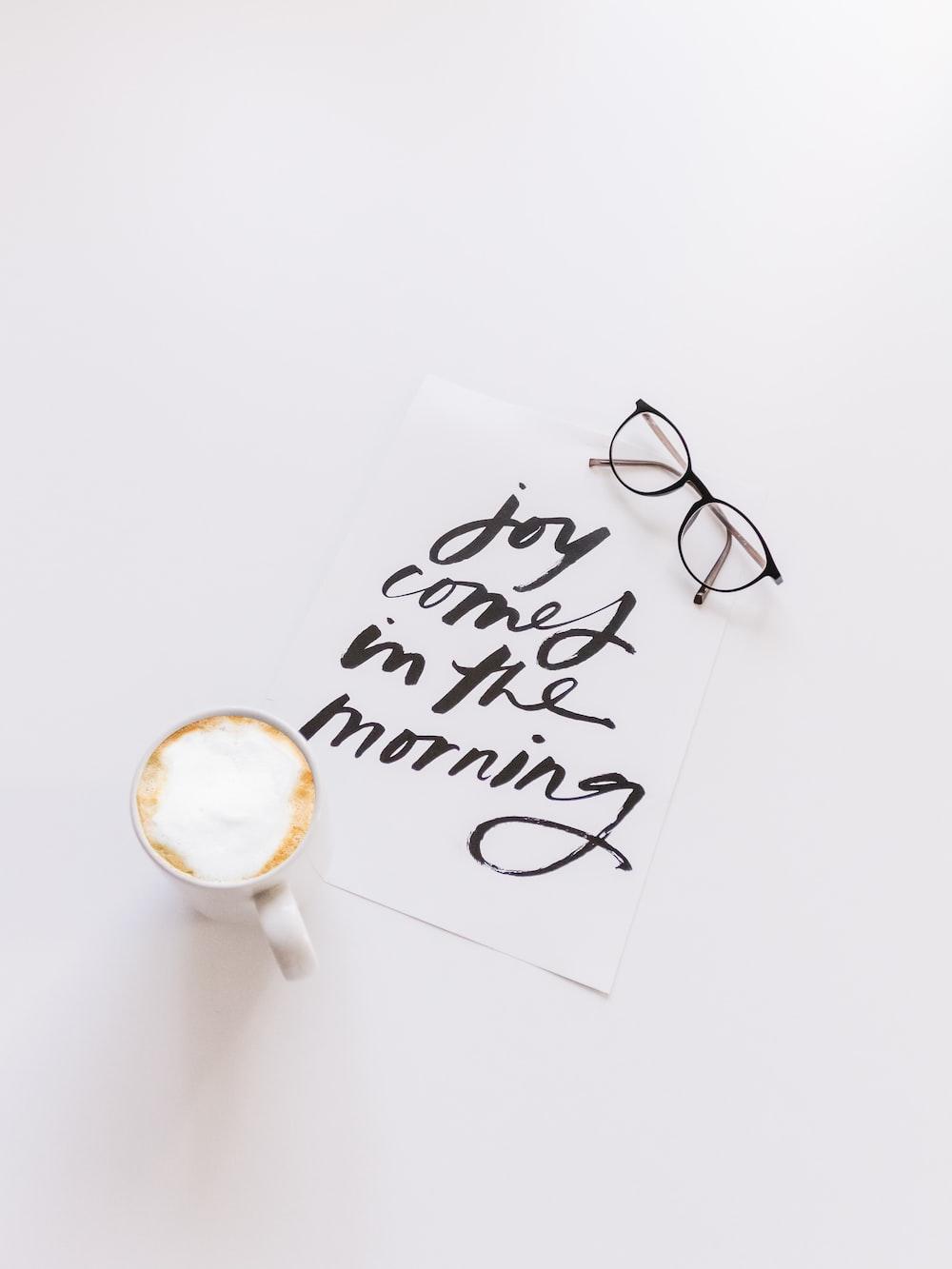 black framed eyeglasses beside white ceramic coffee cup