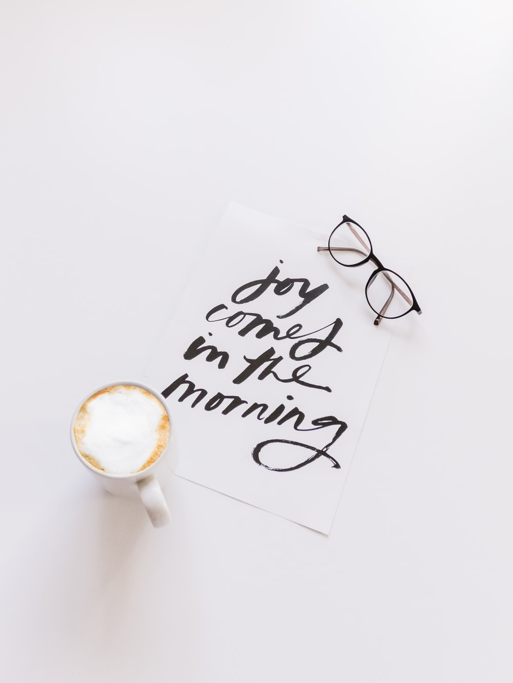 black framed eyeglasses beside white ceramic coffee cup