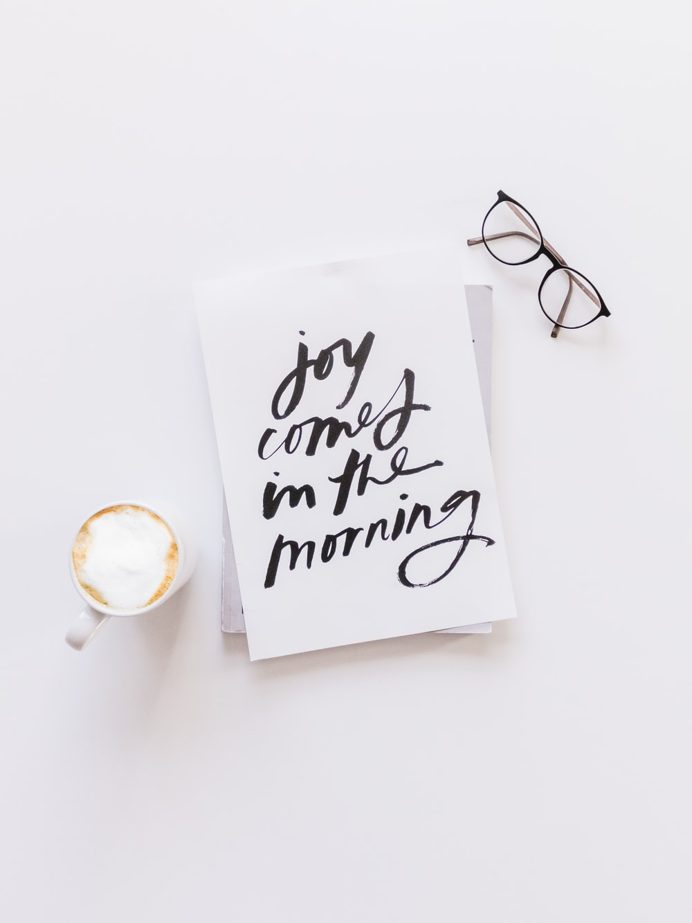 brown framed eyeglasses,latte, and joy comes in the morning note on white surface