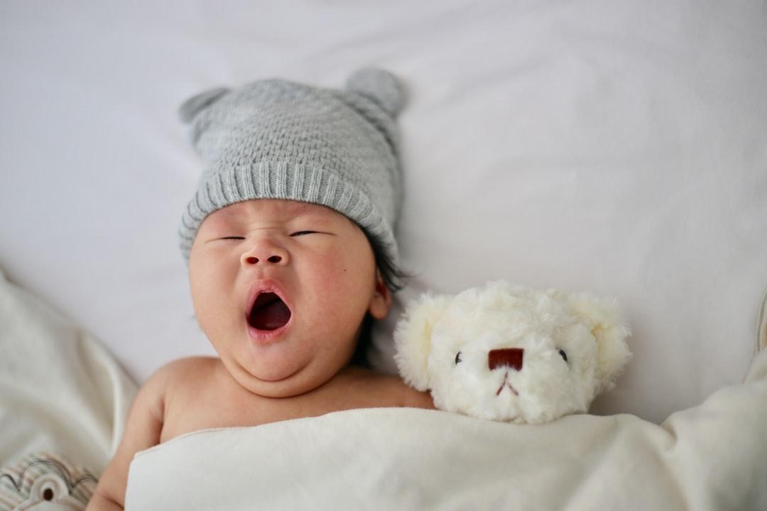 foto de bebê bocejando deitado ao lado de ursinho de pelúcia