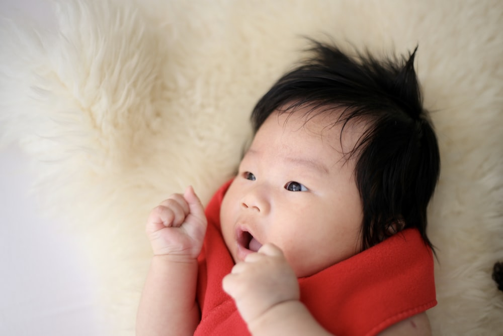 selective focus photography of baby wearing red top