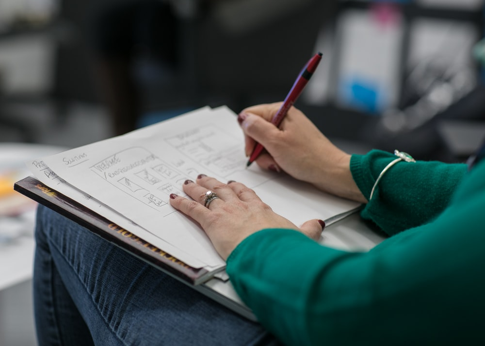 person writing on paper at lap