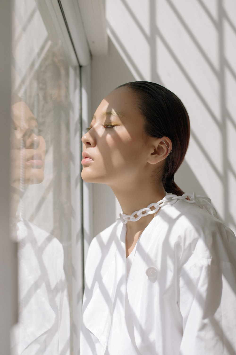 woman standing beside clear glass