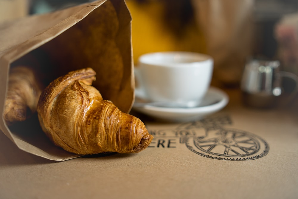 baked bread on paper bag beside white cup and saucer