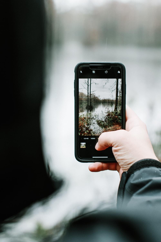 person taking photo of lake