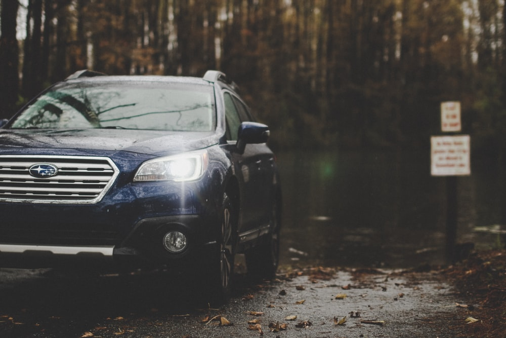 blue Subaru parked near forest