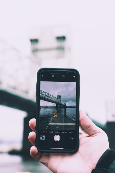 person holding black smartphone taking photo of bridge