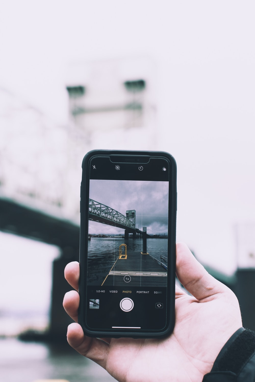 person holding black smartphone taking photo of bridge